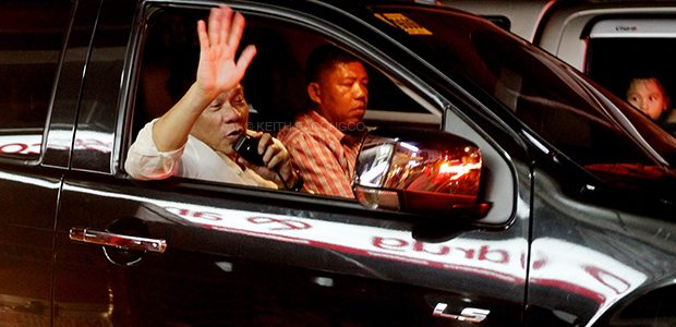 HOME SWEET HOME. President Rodrigo Duterte waves to the bystanders along Quirino Avenue, Davao City on Friday night as his convoy was stuck in a traffic jam. KEITH BACONGCO