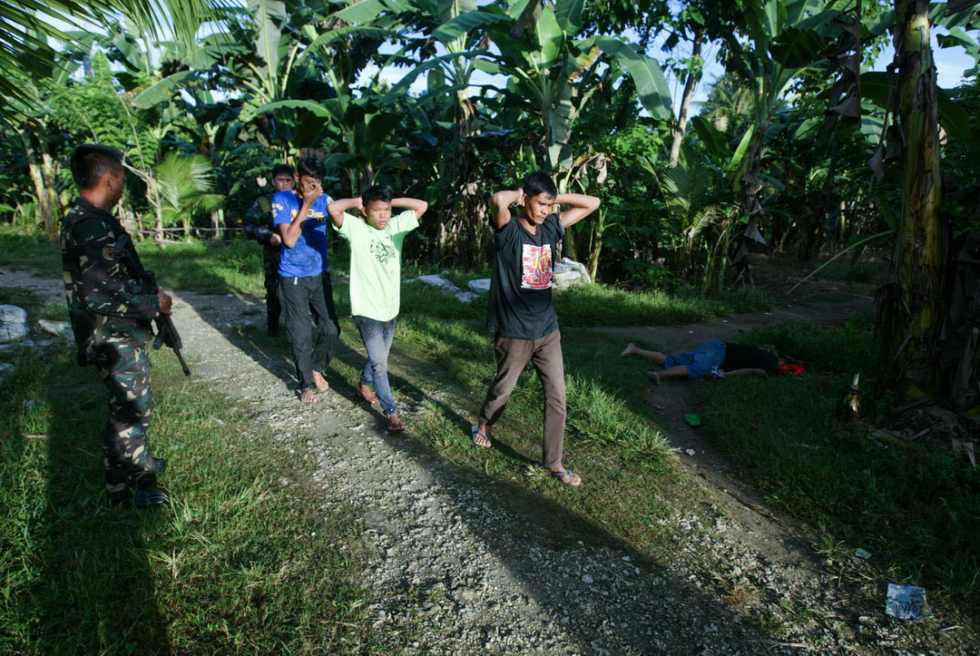 Villagers, who were mistaken as escapees, walk past by the body of Satar Manalundong after an alleged shootout with the police in Barangay Amas, Kidpawan City on January 4, 2017. Manalundong was killed in a police operation hours after the jailbreak at Amas Provincial Jail, where 158 inmates had escaped in an early morning raid orchestrated by suspected Moro rebels.