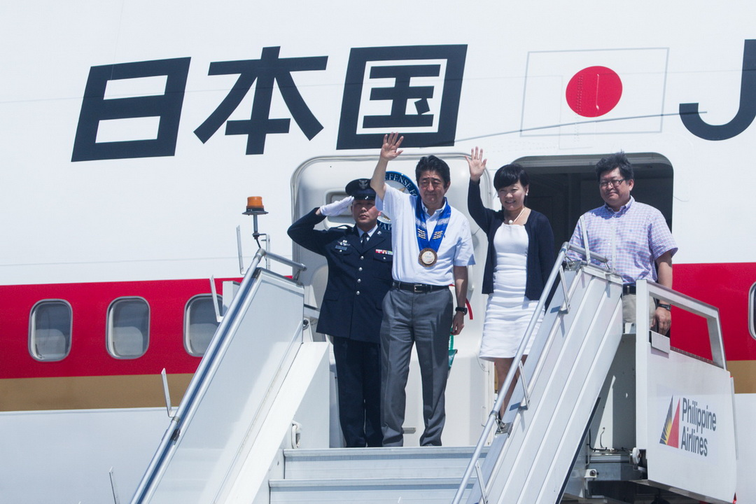 Japan Prime Minister Shinzo Abe and wife Akie wave to the spectators during their departure for Japan following a two-day visit in Davao City on January 12-13, 2017.
