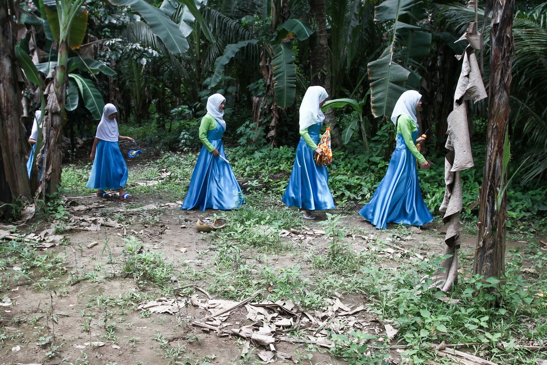 Bridesmaids belonging to the Kagan tribe walk in the middle of a banana plants on their way to a tradiional wedding ceremony in a remote village of Maco in Compostela Valley Province on Sunday, April 2, 2017.