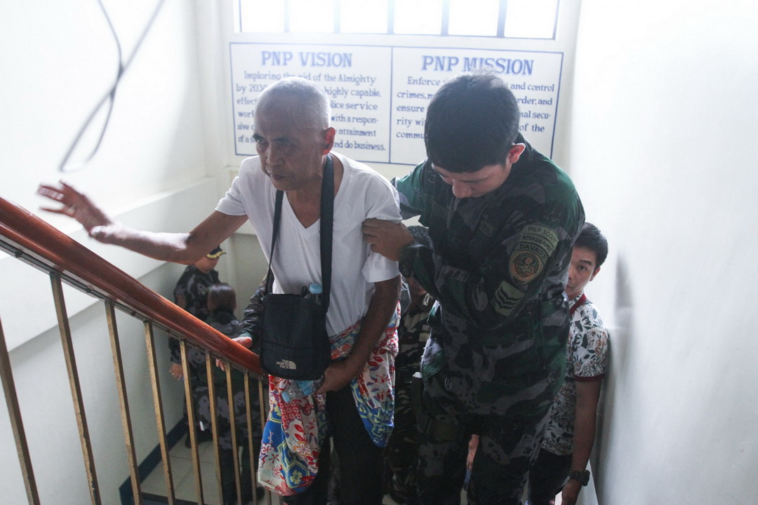 Cayamora Maute (center), father of the Maute brothers, inside the Davao City Police Office on 6 June 2017. Cayamora was arrested at the Sirawan, Toril checkpoint of Task Force Davao.
