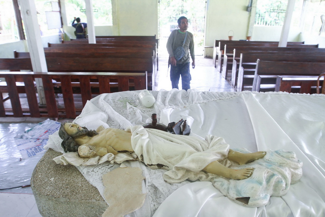 A member of the Barangay Peacekeeping Action Team on June 22 inspects the chapel in Barangay Malagakit in Pigcawayan North Cotabato after it was desecrated by the Bangsamoro Islamic Freedom Fighters on June 21, 2017.