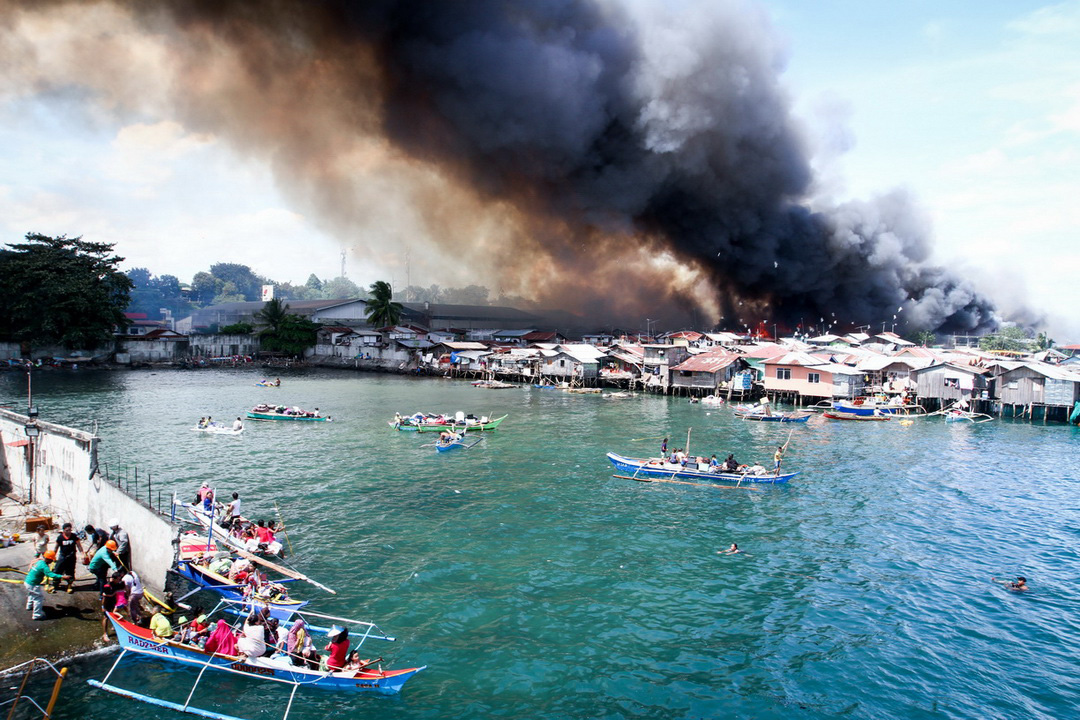 Residents escape on boats as a fire spreads through the coastal village of Sasa in Davao City on November 24, 2017. The fire, which razed least 400 houses, rendered about 800 families homeless.