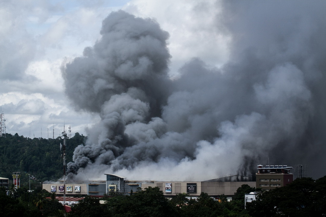 Thick smoke billows from burning NCCC Mall in Davao City on December 23, 2017. Thirty eight persons were killed in the fire after they were trapped in the fourth floor of the mall.