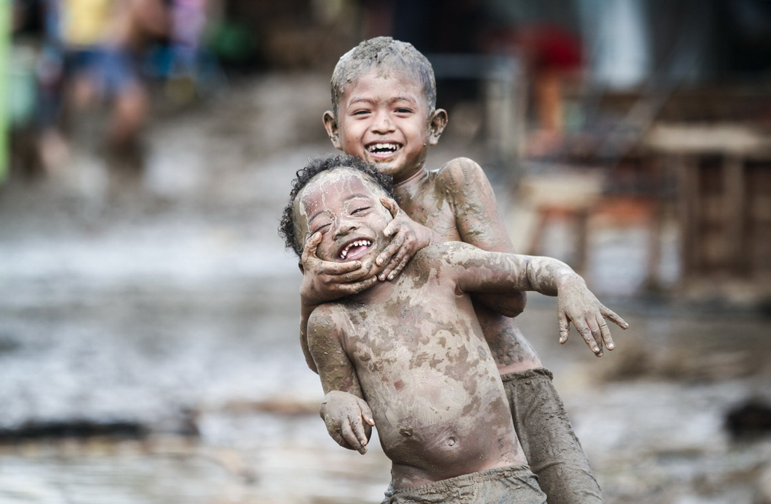 Children play in the mud following a flood that swamped their village in Montevista, Compostela Valley province on December 22, 2017.. Compostela Valley is one of several provinces in Mindanao under Storm Signal No. 2 because of Storm Vinta.