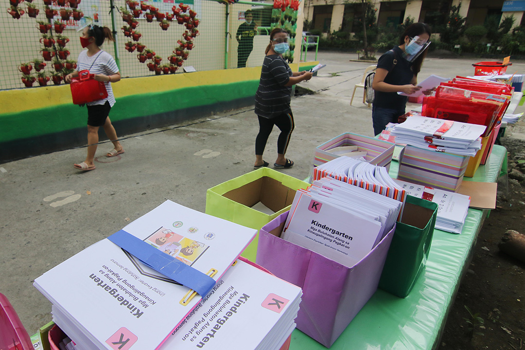 Parents of a kindergarten class drop and collect learning modules at Sta. Ana Central Elementary School in Davao City. The school is implementing a contact-less transaction among parents as a measure against the spread of Covid-19.